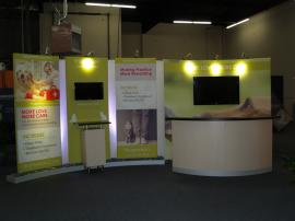 Custom 10 x 20 Exhibit with Large Format Pillowcase Graphics, Closet Storage, Reception Counter, and Pedestal. Re-configures to 10 x 10 -- Image 1
