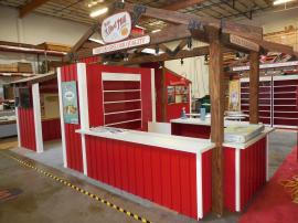 Custom Wood Fabrication Island with Large Fabric and Direct Print Graphics, Storage, Shelving, Seating, and A/V -- Image 1