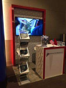 Custom Inline Exhibit with Large Monitor, Counter, and Brochure Stand