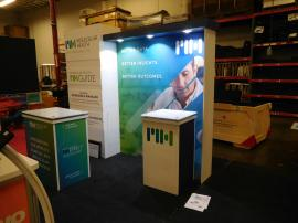 Custom Modular Inline Exhibit with Laminate Panels, SEG Graphic, Puck Lights, and (2) Modular Laminate Counters with Locking Storage